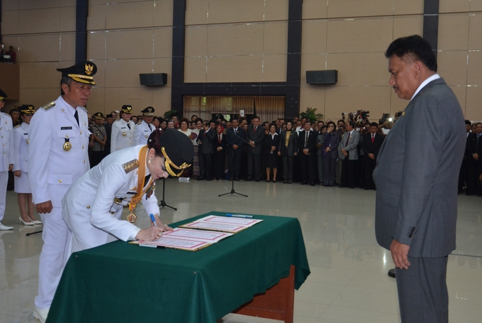 Bupati Minsel Christiany Eugenia Paruntu saat menandatangani berita acara pelantikan dihadapan Gubernur Sulut Olly Dondokambey