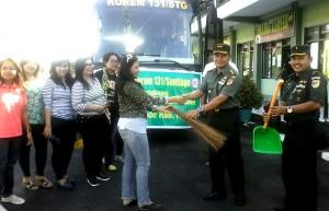Kolonel Ario menyerahkan alat bersih bersih kepada Ketua FJPI Sulut Jeane Rondonuwu